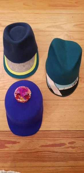 """Drei Kappen aus der Kollektion Winter 20/21: Herrenkopf blau mit 3farbigem Schirm, Herrenkopf petrol mit bunt gemixtem Schirm, Cap """"Dallas"""" aus reiner Wolle mit buntem Pompom"""